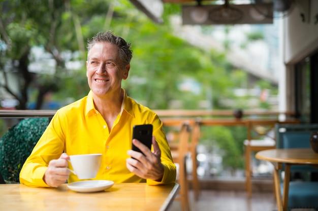 Oudere man zit in coffeeshop en denken tijdens het gebruik van mobiele telefoon