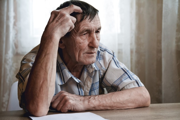 Oudere man zit met zijn hoofd, lijdt aan geheugenverlies