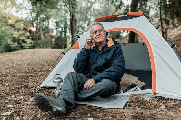 Oudere man zoekt internetverbinding in het bos