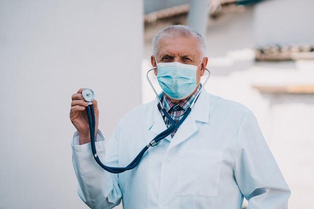 Oudere mannelijke arts in een witte jas en een medisch masker op zijn gezicht toont een stethoscoop om het werk van de longen en het hart van patiënten te onderzoeken