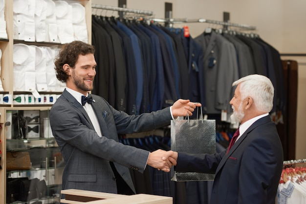 Oudere mens die hand geeft aan het glimlachen aan verkoper.