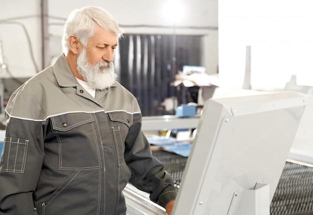 Oudere mens die het grijze eenvormige werken aan fabriek dragen