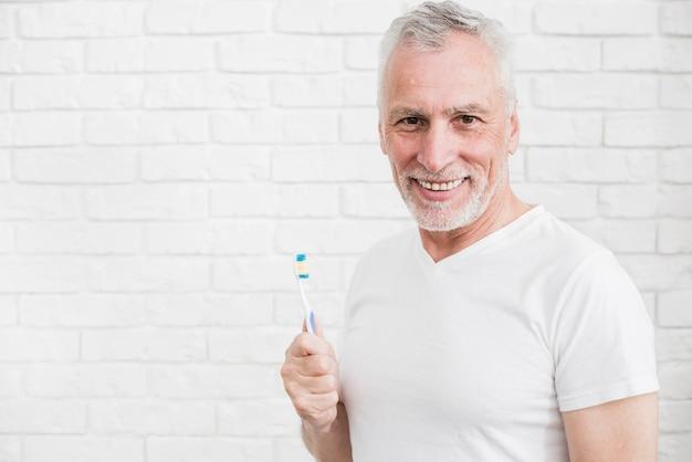 Oudere mens die zijn tanden wast
