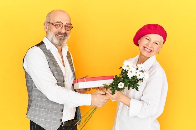 Oudere mensen, leeftijd, dating, romantiek en relaties concept. opgewonden, verward vrouw van middelbare leeftijd met rode motorkap die zich ongemakkelijk voelt terwijl ze een onverwacht cadeau en bloemen ontvangt van een senior bebaarde man