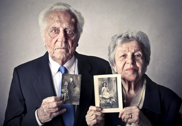 Oudere mensen met foto's van zichzelf