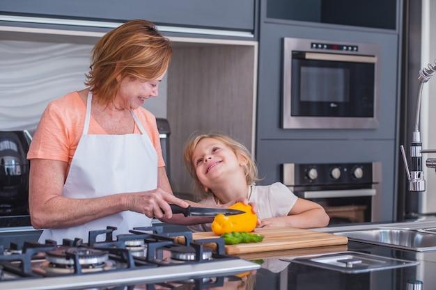 Oudere moeder en dochtertje samen koken. moeder en dochter snijden groenten om te koken