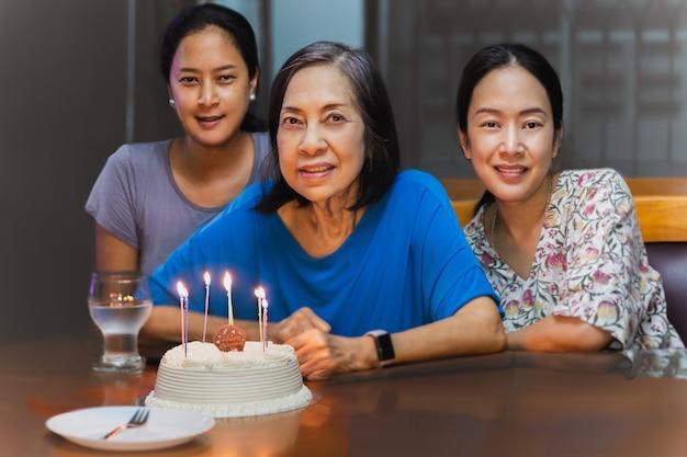 Oudere moeder en twee volwassen dochters vieren een verjaardag met verjaardagstaart