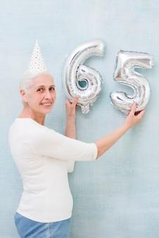 Oudere mooie vrouw die het metaalnummer van de folieballon op haar verjaardag houden