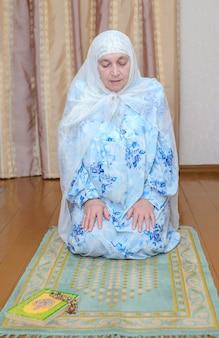 Oudere moslimvrouw in een felblauwe jurk en een witte sjaal bidt op de groene gebedsmat