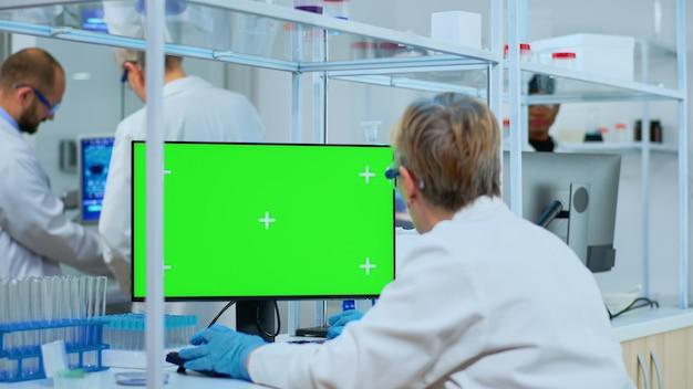 Oudere onderzoeker die naar chroma key-display kijkt in een modern uitgerust laboratorium. multi-etnisch team van microbiologen die vaccinonderzoek doen en schrijven op apparaat met groen scherm, geïsoleerd, mockup-display.