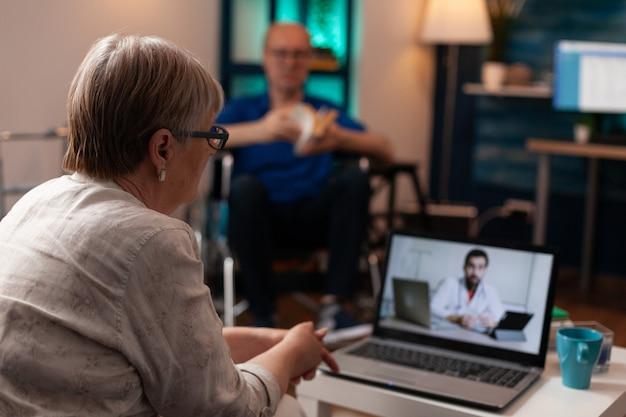 Oudere onwel vrouw belt arts in kliniek met behulp van videogesprek