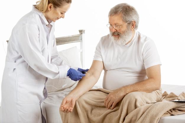 Oudere oude man herstellende in een comfortabel ziekenhuisbed geïsoleerd op wit