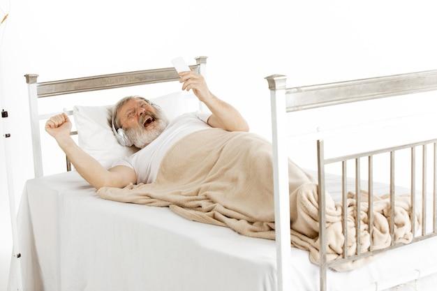 Oudere oude man herstellende in een ziekenhuisbed geïsoleerd op wit