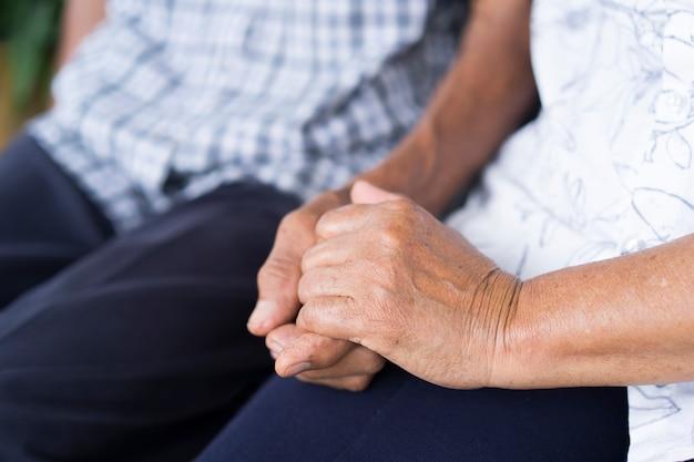 Oudere paren die oudere handen houden en samen zitten. concept van zorg samen.