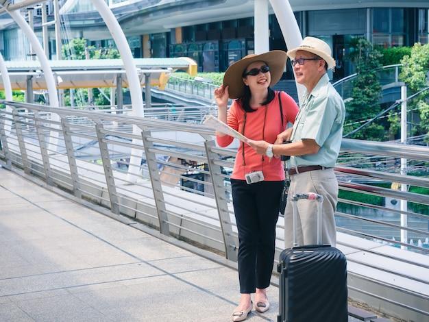 Oudere paren reizen in de stad, het oude echtpaar kijken naar de kaart