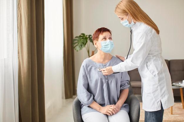 Oudere patiënt met medisch masker wordt gecontroleerd door de vrouwelijke arts van het covid-herstelcentrum