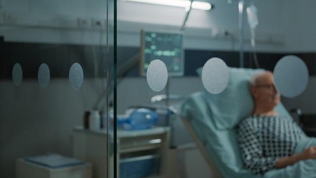Oudere patiënt met ziekte zittend in ziekenhuisafdeling