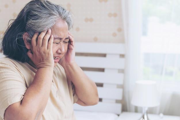 Oudere patiënten in bed, aziatische hogere de hoofdpijnhanden van vrouwenpatiënten op voorhoofd - medisch en gezondheidszorgconcept