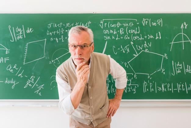 Oudere professor in klaslokaal camera kijken met vraag