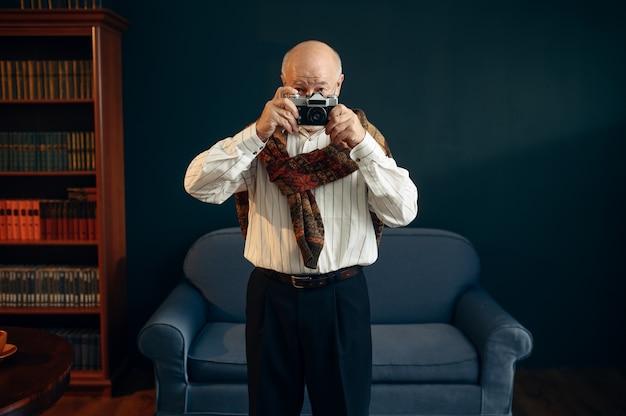 Oudere schrijver houdt retro fotocamera in kantoor aan huis. oude man met bril schrijft literatuurroman in kamer met rook