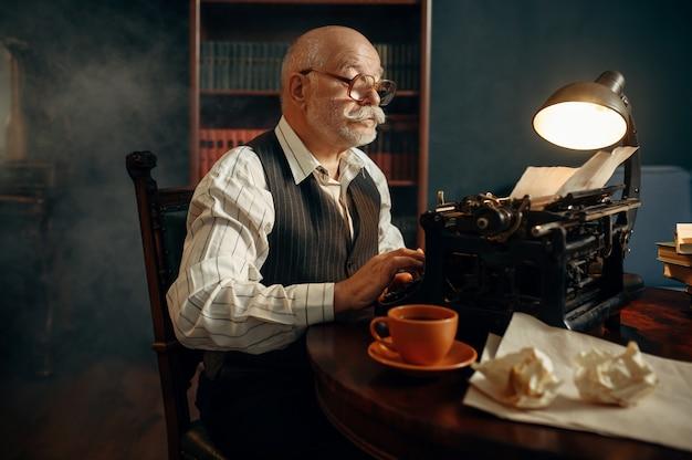 Oudere schrijver werkt op vintage typemachine in zijn kantoor aan huis. oude man met bril schrijft literatuurroman in kamer met rook