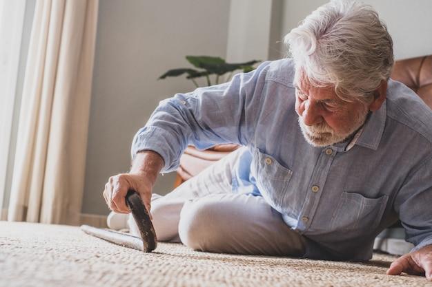 Oudere senior man liggend op de vloer na een val met houten wandelstok naast de bank op tapijt in de woonkamer thuis. oude man die pijn heeft en moeite heeft om op te staan nadat hij thuis is gevallen