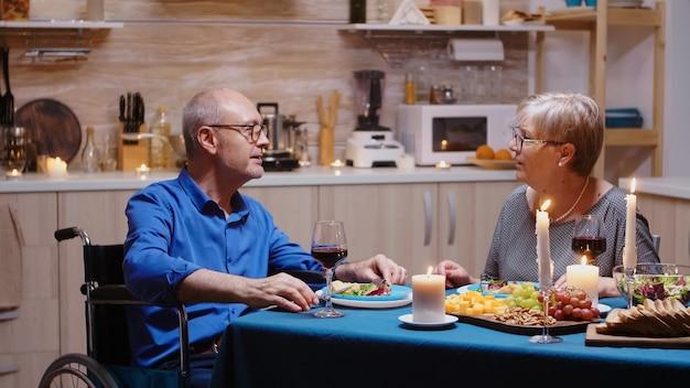 Oudere senior man met een handicap met een romantisch diner aan tafel in een gezellige keuken. rolstoel geïmmobiliseerd verlamde gehandicapte man dineren met vrouw thuis, genietend van de maaltijd
