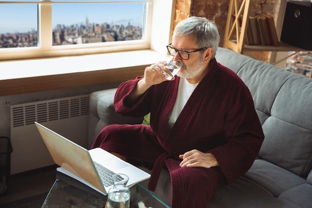 Oudere senior oudere man tijdens quarantaine, beseffend hoe belangrijk thuis blijven tijdens virusuitbraak