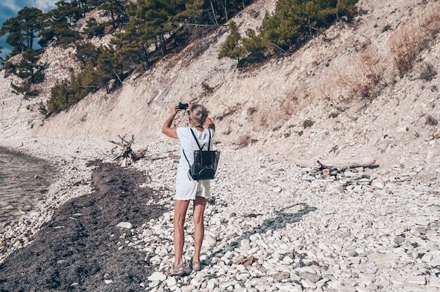 Oudere senior reizende backpacker volwassen vrouw toerist wandelen fotograferen op kust