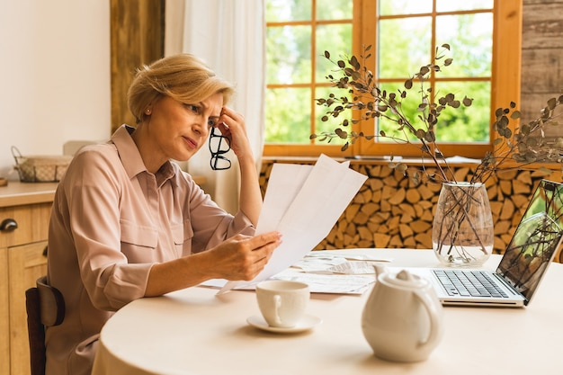 Oudere senior vrouw van middelbare leeftijd met papieren rekening of brief met behulp van laptopcomputer thuis voor het doen van online betalingen op de website, het berekenen van de kosten van financiële belastingen, het herzien van de bankrekening.