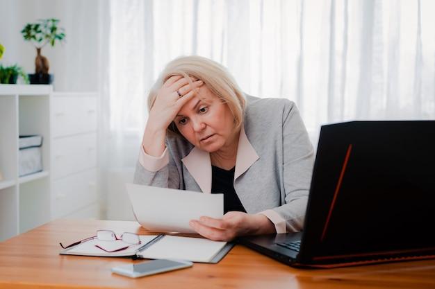 Oudere senior vrouw worstelt met de computer met papieren documenten, verbaasd over de zakelijke beslissing