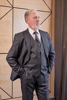 Oudere stafmedewerker in elegant grijs pak hand in hand in de zak, poseren, kant binnenshuis kijken, na vergadering. mensen bedrijfsconcept
