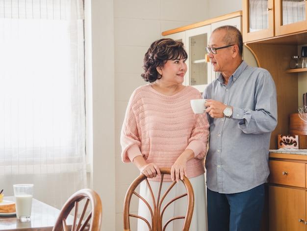 Oudere stellen staan 's ochtends koffie te drinken in de keuken