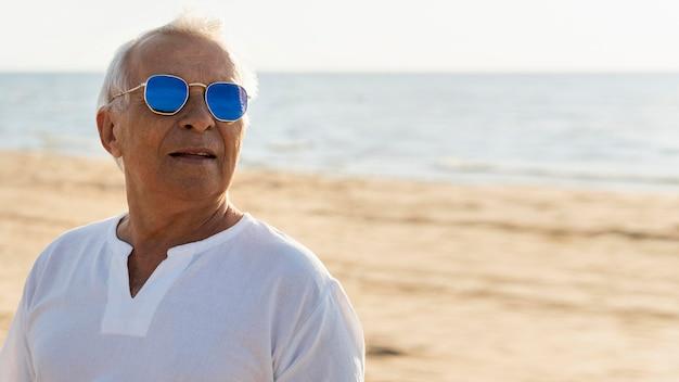 Oudere stijlvolle man met zonnebril poseren aan het strand