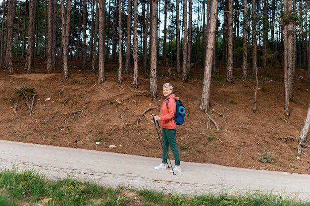Oudere toeristenvrouw met wandelstokken in het bos