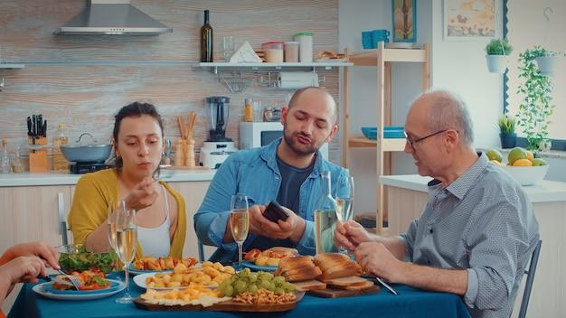 Oudere vader kijkt naar foto's op smartphone van jonge man terwijl hij in de keuken zit tijdens het familiediner. meerdere generaties, twee stellen praten en eten tijdens een gastronomische man, genietend van de tijd thuis