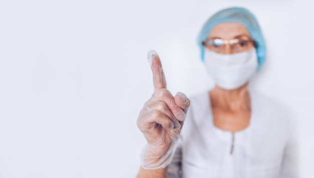 Oudere volwassen vrouw arts of verpleegkundige opgeheven vinger in een witte medische jas, handschoenen, gezichtsmasker dragen van persoonlijke beschermingsmiddelen geïsoleerd. gezondheidszorg en geneeskunde concept. covid-19 pandemische crisis