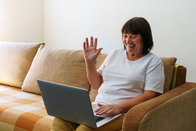 Oudere volwassen vrouw die draadloze laptop-apps gebruikt die op internet surfen, zittend op de bank glimlachend van middelbare leeftijd