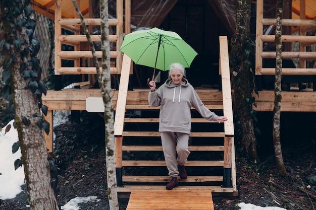 Oudere volwassen vrouw met paraplu bij glamping camping tent. moderne vakantie levensstijl concept.