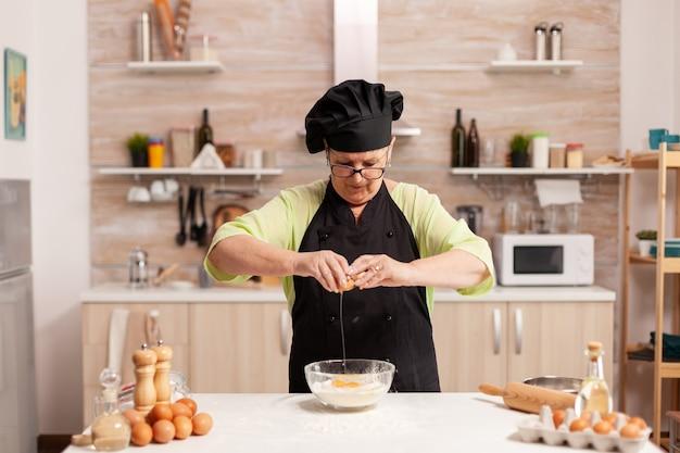 Oudere vrouw bereidt deeg krakende eieren over tarwemeel volgens traditioneel recept. oudere banketbakker die ei op glazen kom kraakt voor cakerecept in keuken, met de hand mengen, kneden.