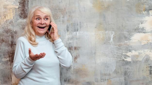 Oudere vrouw bij bevroren venster dat over telefoon spreekt