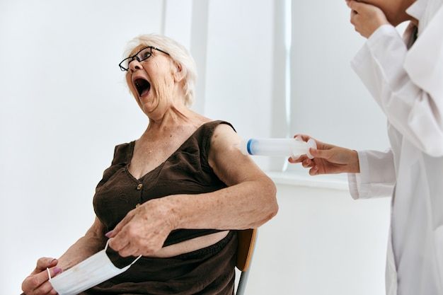 Oudere vrouw bij de doktersafspraak spuitinjectie ziekenhuis