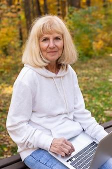 Oudere vrouw buiten in de natuur met laptop