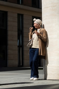 Oudere vrouw buiten in de stad die aan de telefoon praat terwijl ze koffie drinkt
