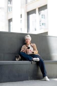 Oudere vrouw buiten in de stad zittend op een bankje en het gebruik van smartphone