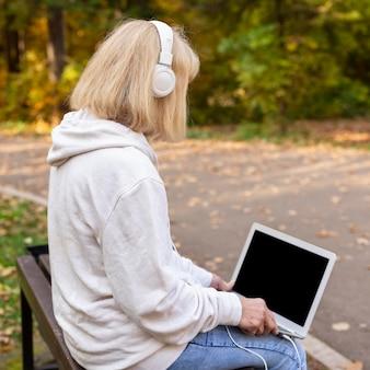 Oudere vrouw buitenshuis met laptop en koptelefoon