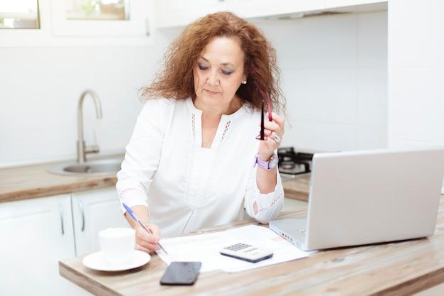 Oudere vrouw concentreerde zich op het herzien van papieren en rekeningen.