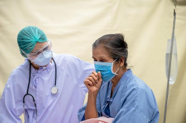 Oudere vrouw, de dokter onderzoekt de symptomen van hoest van de patiënt in het veldhospitaal. beiden droegen maskers vanwege de covid 19-epidemie.