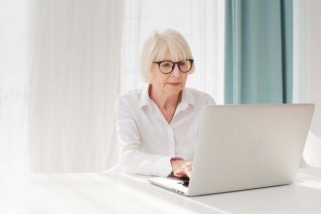 Oudere vrouw die aan laptop in haar bureau werkt