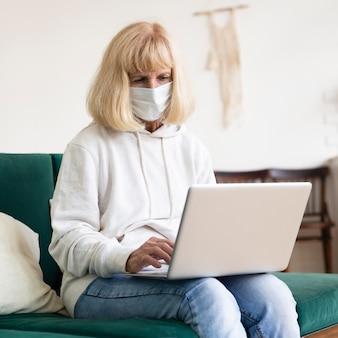 Oudere vrouw die aan laptop thuis werkt terwijl het dragen van medisch masker